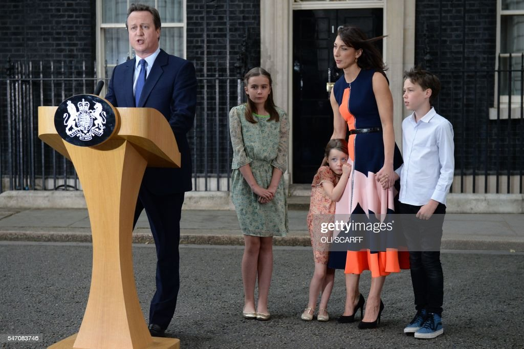 TOPSHOT - Outgoing British prime minister David Cameron speaks beside (L-R) his daughter Nancy Gwen, daughter Florence Rose Endellion, his wife Samantha Cameron and son Arthur Elwen outside 10 Downing Street in central London on July 13, 2016 before going to Buckingham Palace to tender his resignation to Queen Elizabeth II. Outgoing British prime minister David Cameron urged his successor Theresa May on Wednesday to maintain close ties with the EU even while negotiating to leave it, as he paid a fond farewell to MPs hours before leaving office. Cameron will tender his resignation on July 13 to Queen Elizabeth II at Buckingham Palace, after which the monarch will task the new leader of the Conservative Party Theresa May with forming a government. SCARFF