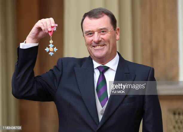 Outgoing Chairman of the All England Lawn Tennis and Croquet Club Philip Brook poses with his medal after he was appointed a Commander of the Order...