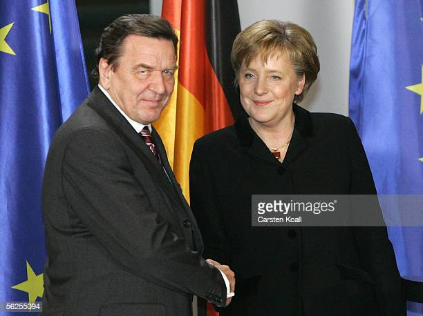 Outgoing Chancellor Gerhard Schroeder shakes hands with newly appointed German Chancellor Angela Merkel at the Chancellery on the day of her official...
