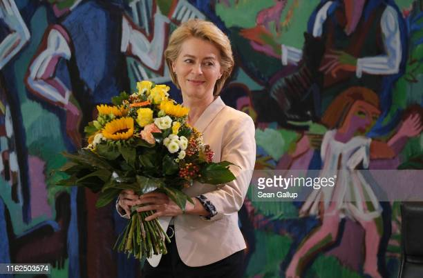 Outgoing Defense Minister Ursula von der Leyen smiles after receiving flowers from German Chancellor Angela Merkel at the weekly government cabinet...