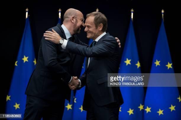 Outgoing European Council President Donald Tusk and newly appointed European Council President Charles hug during the handover ceremony between Tusk...