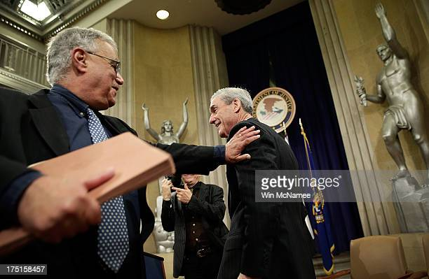 Outgoing FBI Director Robert Mueller gets a pat on his back following his farewell ceremony at the Department of Justice August 1 2013 in Washington...