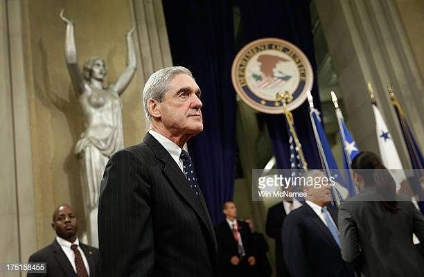 Outgoing FBI Director Robert Mueller leaves the stage following his farewell ceremony at the Department of Justice August 1 2013 in Washington DC...