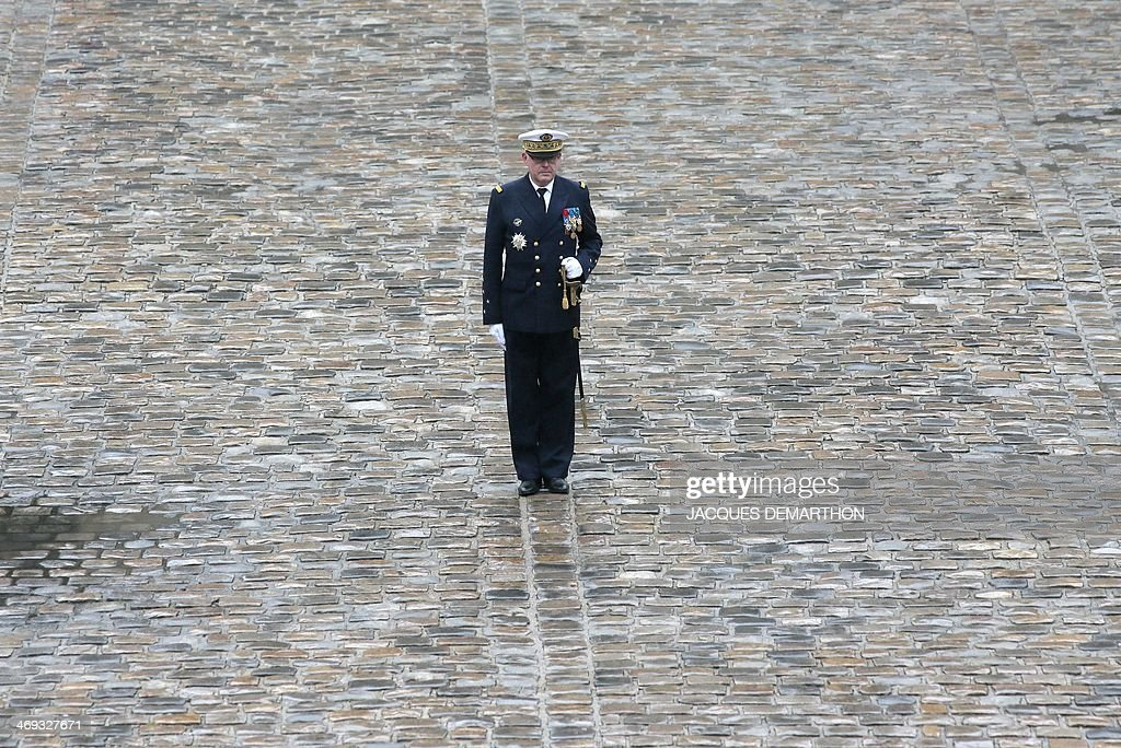 Outgoing French Chief of the Defence Staff, Admiral Edouard Guillaudat (C), stands at attention during a military ceremony in his honour at L'Hotel national des Invalides in Paris on February 14, 2014.