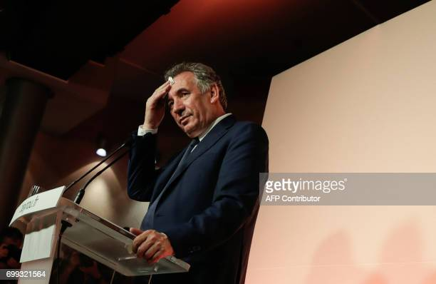 Outgoing French Minister of Justice and Leader of the French MoDem centrist party Francois Bayrou wipes his face as he addresses media...