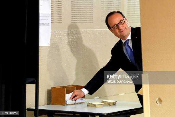 Outgoing French president Francois Hollande takes ballots as he prepares to vote at a polling station in Tulle central France on May 7 during the...