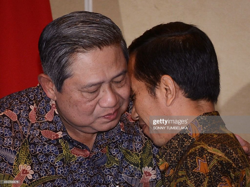 Outgoing Indonesian President Susilo Bambang Yudhoyono (L) and president-elect Joko Widodo (R) embrace after a joint press conference in Nusa Dua, Indonesia's resort island of Bali on August 27, 2014, following their one-on-one meeting to discuss a smooth government transition programme. With a legal challenge by his rival defeated, Widodo popularly known by his nickname Jokowi has swept away the last barrier to the presidency and an ambitious reform agenda after an unlikely rise from his upbringing in a riverside slum. Jokowi will take over from Yudhoyono during the October 20, 2014 inauguration.