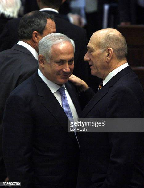 Outgoing Israeli Prime Minister Ehud Olmert speaks with incoming Prime Minister Benjamin Netanyahu during the swearing of a new government in the...