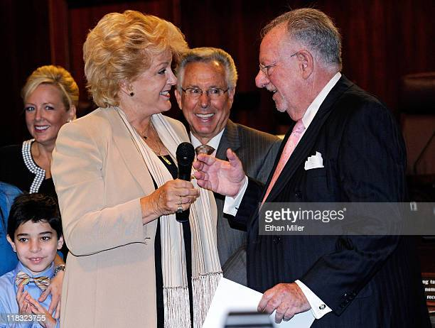Outgoing Las Vegas Mayor Oscar Goodman hands a microphone to his wife Carolyn Goodman after swearing her in as the new mayor as outgoing Mayor Pro...