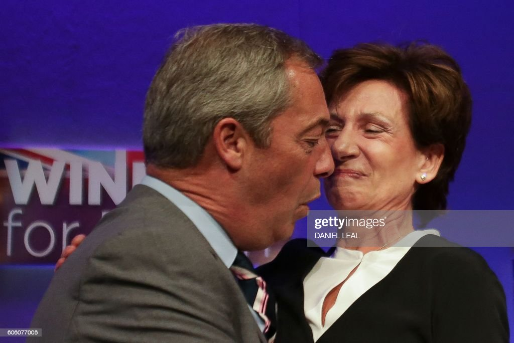 Outgoing leader Nigel Farage (L) embraces new leader of the anti-EU UK Independence Party (UKIP) Diane James (R) as she is introduced at the UKIP Autumn Conference in Bournemouth, on the southern coast of England, on September 16, 2016. Diane James was announced as UKIP's new leader on September 16 to replace charismatic figurehead Nigel Farage. Farage made the shock decision to quit as leader of the UK Independence Party following victory in the referendum on Britain's membership of the European Union. / AFP / Daniel Leal-Olivas