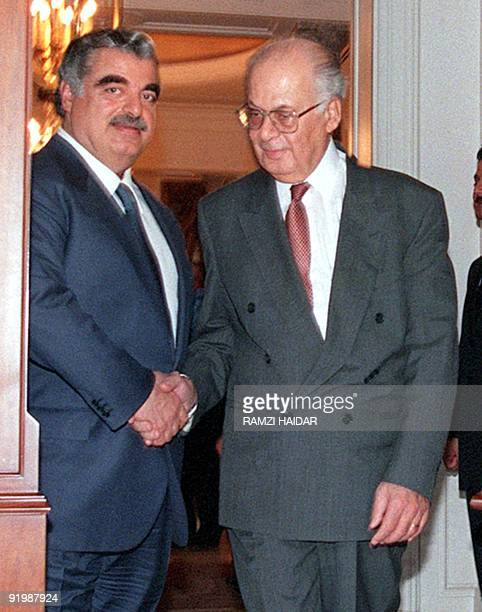 Outgoing Lebanese Prime Minister Rafic Hariri shakes hands with Prime Ministerdesignate Salim Hoss 02 December after their meeting in Beirut Hoss was...