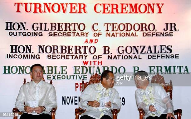 Outgoing Philippine Defence Secretary Gilberto Teodoro sits together with his replacement Norberto Gonzales and Executive Secretary Eduardo Ermita...