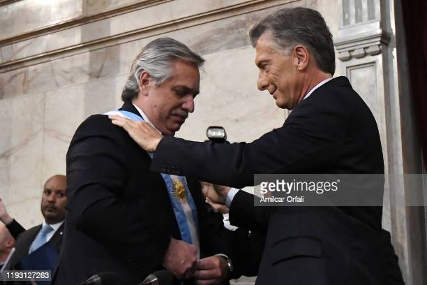 Outgoing President of Argentina Mauricio Macri puts the presidential sash to Argentina Presidentelect Alberto Fernandez during the Presidential...