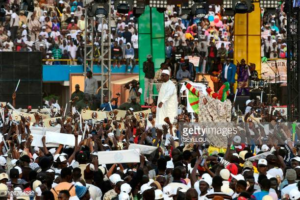 Outgoing Senegalese president and candidate Macky Sall greets supporters as he arrives at the Leopold Sedar Senghor stadium for his last meeting...