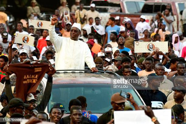 Outgoing Senegalese president and candidate Macky Sall waves to supporters from his car as he arrives at the Leopold Sedar Senghor stadium for his...