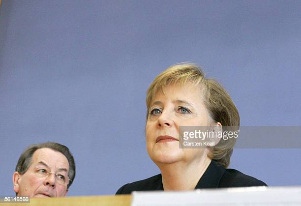 Outgoing SPD leader Franz Muentefering and incoming Chancellor Angela Merkel of the conservative Christian Democratic Union give a joint press...