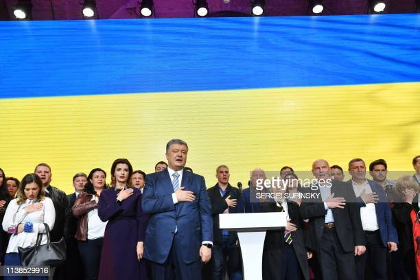 Outgoing Ukrainian President Petro Poroshenko and his team sing the state anthem at the party headquarters in Kiev on April 21 at the end of a day of...