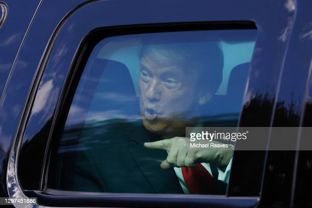 Outgoing US President Donald Trump waves to supporters lined along on the route to his Mar-a-Lago estate on January 20, 2021 in West Palm Beach,...