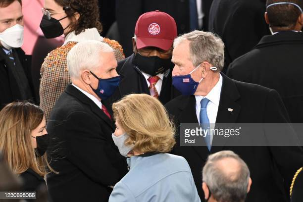 Outgoing US Vice President Mike Pence talks with Former US President George W. Bush during the 59th Presidential Inauguration at the U.S. Capitol on...