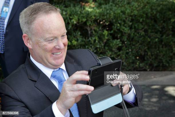 Outgoing White House Press Secretary Sean Spicer takes photographs for friends before President Donald Trump departs the White House July 25 2017 in...