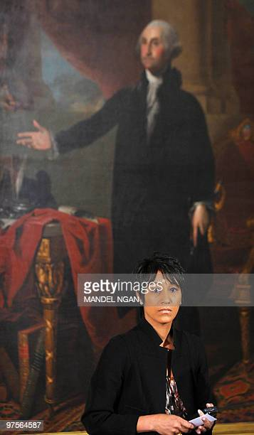 Outgoing White House Social Secretary Desiree Rogers stands beneath a portrait of George Washington before the start of a reception marking...