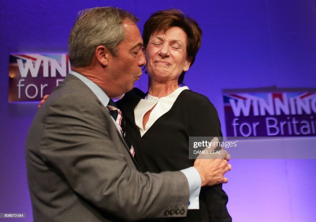 TOPSHOT - Outgoinng leader Nigel Farage (L) embraces new leader of the anti-EU UK Independence Party (UKIP) Diane James (R) as she is introduced at the UKIP Autumn Conference in Bournemouth, on the southern coast of England, on September 16, 2016. Diane James was announced as UKIP's new leader on September 16 to replace charismatic figurehead Nigel Farage. Farage made the shock decision to quit as leader of the UK Independence Party following victory in the referendum on Britain's membership of the European Union. OLIVAS
