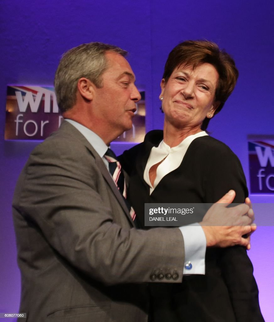 Outgoinng leader Nigel Farage (L) embraces new leader of the anti-EU UK Independence Party (UKIP) Diane James (R) as she is introduced at the UKIP Autumn Conference in Bournemouth, on the southern coast of England, on September 16, 2016. Diane James was announced as UKIP's new leader on September 16 to replace charismatic figurehead Nigel Farage. Farage made the shock decision to quit as leader of the UK Independence Party following victory in the referendum on Britain's membership of the European Union. / AFP / Daniel Leal-Olivas