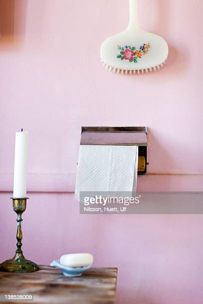 Outhouse toilet paper beside candle