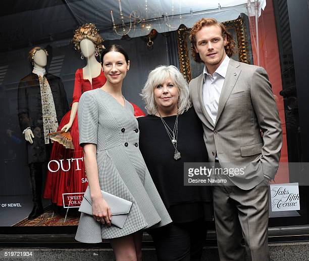 'Outlander' Costume Designer Terry Dresbach poses with actors Caitriona Balfe and Sam Heughan during Saks Fifth Avenue 'Outlander' Window Display...