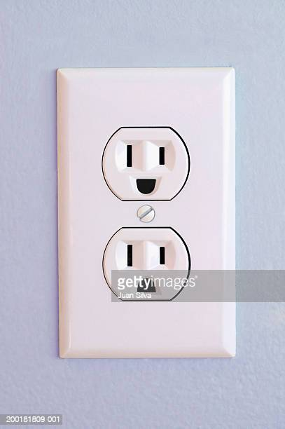 Outlet on wall with happy and sad face (Digital Composite)