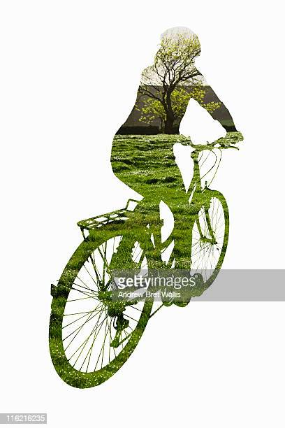 outline of female cyclist against green landscape