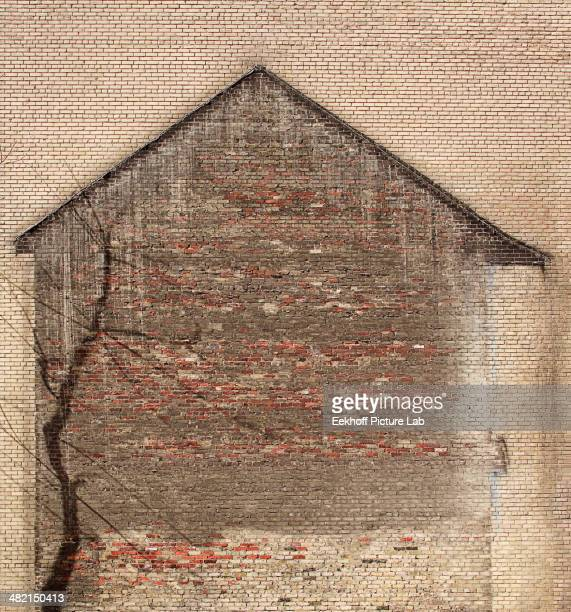 Outline of house on brick wall