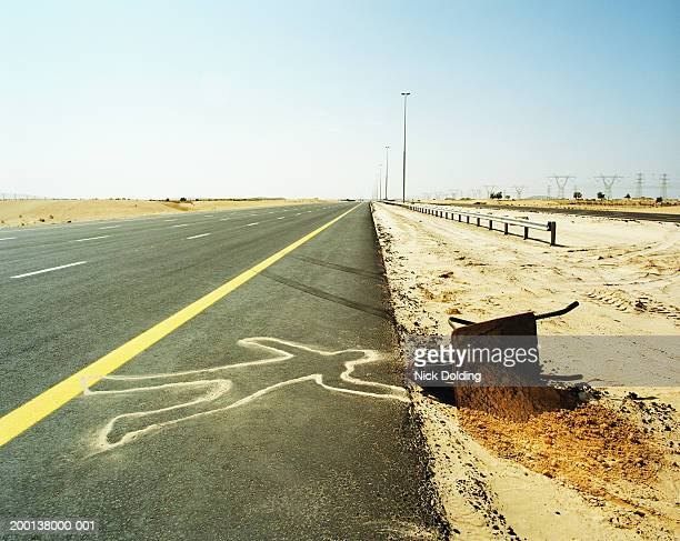 outline of person on highway by overturned wheelbarrow - dead body stock pictures, royalty-free photos & images
