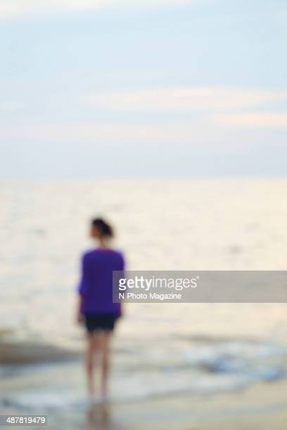 Outoffocus portrait of a woman standing on a beach at sunset taken on July 22 2013