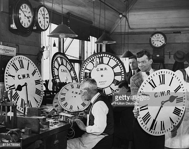 Outoforder clocks from Great Western Railway stations are repaired in a shop in Reading Berkshire England March 2 1934