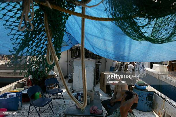 Outofwork Vietnamese shrimp fishermen sit on their boats after their homes were destroyed by Hurricane Katrina September 11 2005 in Biloxi...