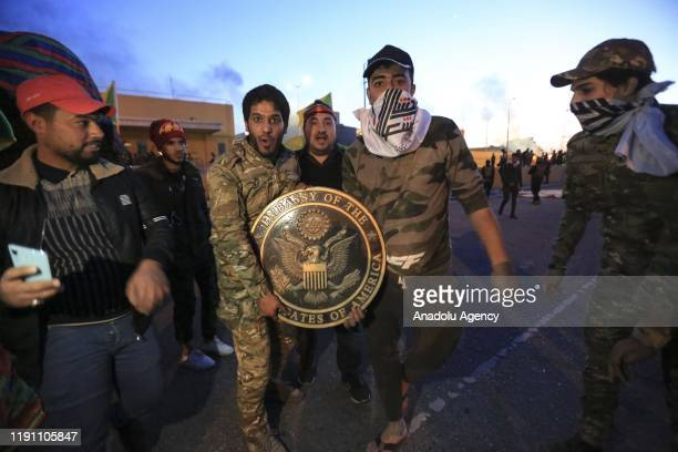 Outraged Iraqi protesters pose for a photo with US Embassy plaque as they storm the US Embassy in Baghdad protesting Washington's attacks on armed...