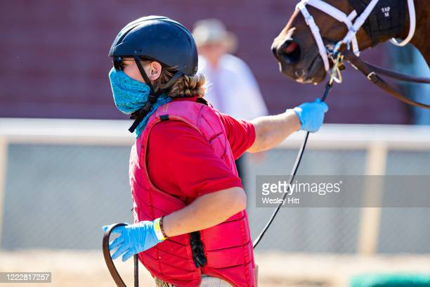 Outrider leads a horse into the starting gate during the Covid19 Pandemic on Derby Day at Oaklawn Racing Casino Resort on May 2 2020 in Hot Springs...