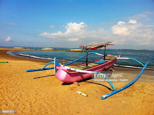 Outrigger Boat Moored At Beach Against Blue Sky