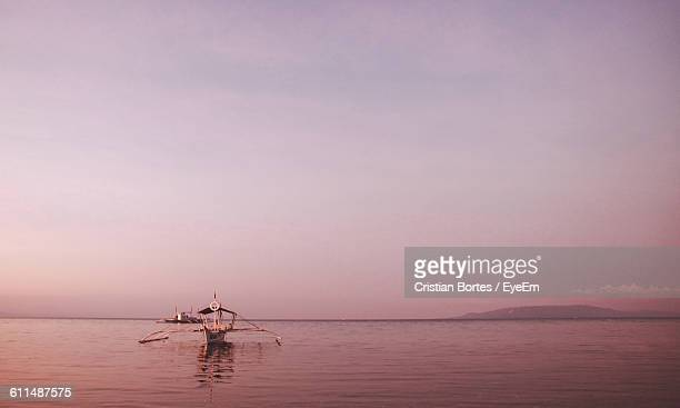 outrigger boat sailing on lake against sky during sunset - bortes cristian stock photos and pictures