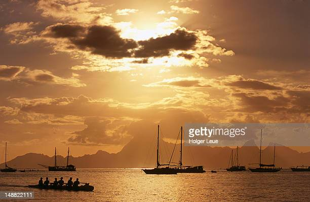 Outrigger canoe, sailboats and Moorea Island at sunset.