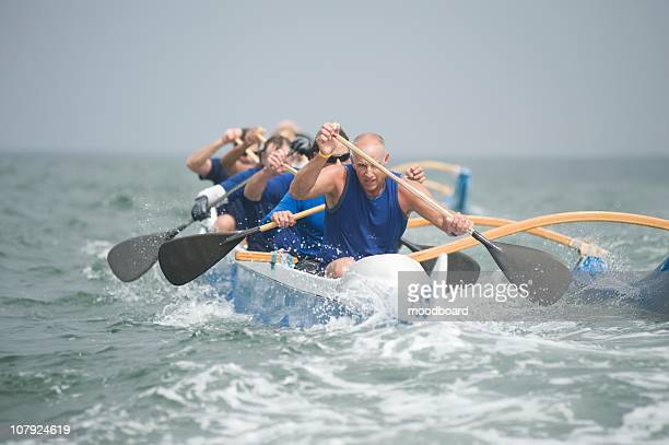 outrigger canoeing team on water - sport rowing stock pictures, royalty-free photos & images
