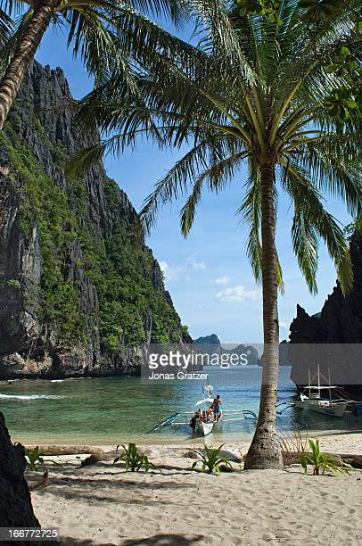 Outrigger canoes among the islands of El Nido in the Palawan archipelago. El Nido is considered as a showcase of Palawan's geology and diverse...