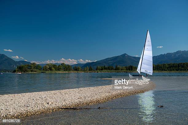 Outrigger sailboat moored on lakeshore against blue sky, Lake Chiemsee, Bavaria, Germany