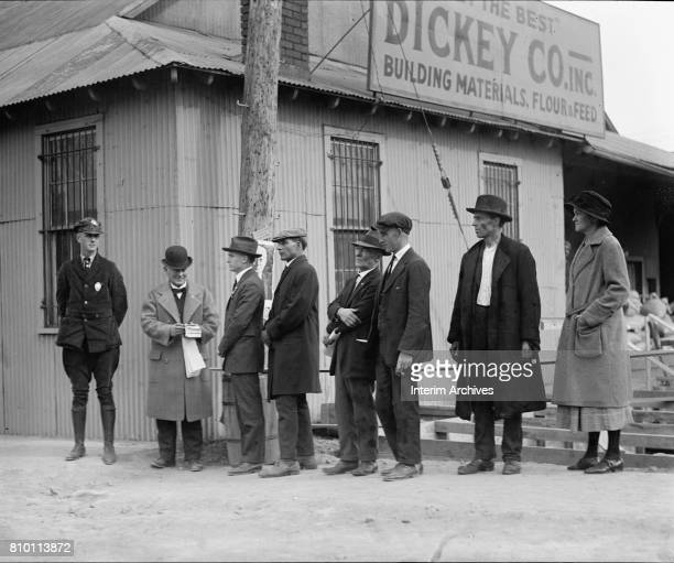 Outside a building materials and feed supply store, a police officer watches as an official hands out ballots to a line of prospective voters during...