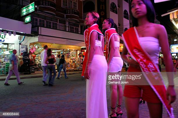 Outside a gogo bar on Walking Street in Pattaya sexily dressed girls try to entice customers by flashing their welcoming smiles and shouting...