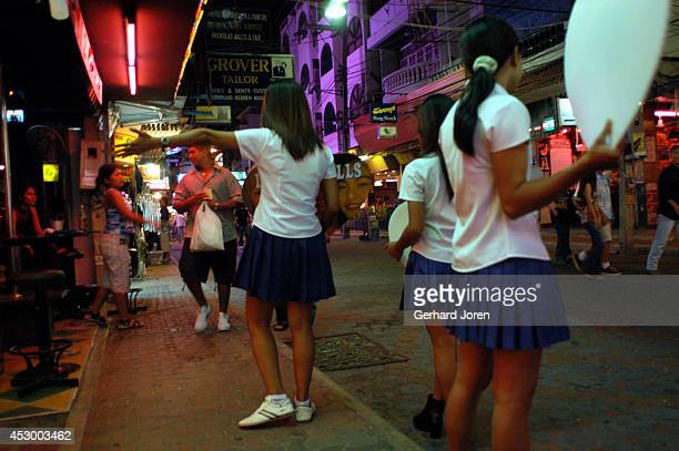 Outside a gogo bar on Walking Street in Pattaya sexily dressed girls try to entice customers by flashing their welcoming smiles holding advertising...