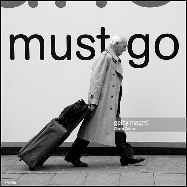 "Outside a shop having a sale saying; ""Everything must go"" This man is pulling a suitcase on his way to or from a station in Oxford Street."