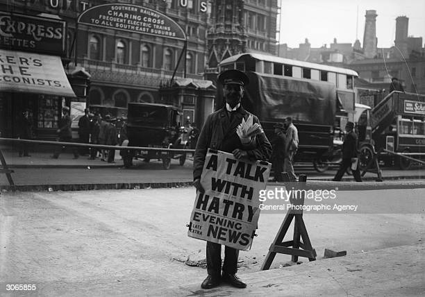 Outside Charing Cross station an Evening News newspaper vendor carries a poster saying A Talk With Hatry'', referring to financier Clarence Charles...