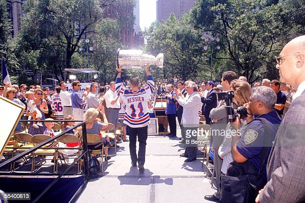 Outside City Hall hockey player Mark Messier of the New York Rangers holds the Stanley Cup aloft and approaches a podium as a crowd of onlookers clap...
